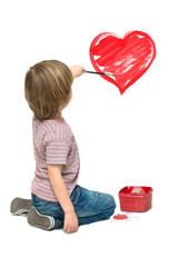 Little boy painting a red heart on the wall