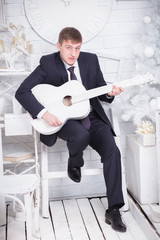 man in a suit playing guitar