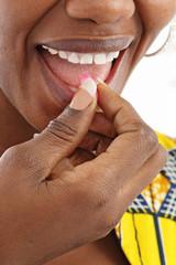 femme noire avalant médicament
