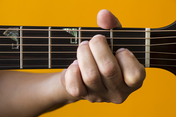 Hand performing E chord on guitar