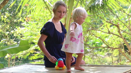 little blonde girl dancing and takes small toy car near mother