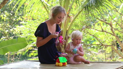mother blowing soap bubbles for her daughter and gives her a toy