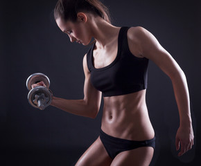 sexy young fit woman lifting dumbell