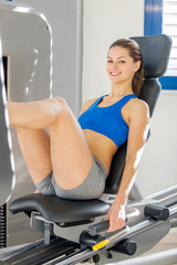 attractive smiling woman is doing exercises for her legs in the