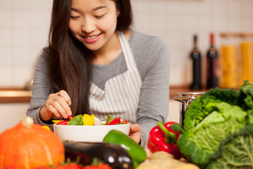asian smiling woman is composing a colorful salad