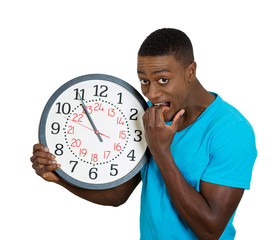 man with clock stressed biting fingernails pressured by time