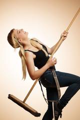 Frau spiele Luftgitarre mit Besen