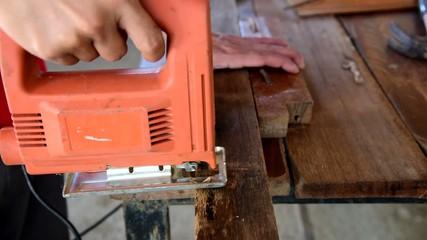 carpenter sawing wood stick by electrics jig saw