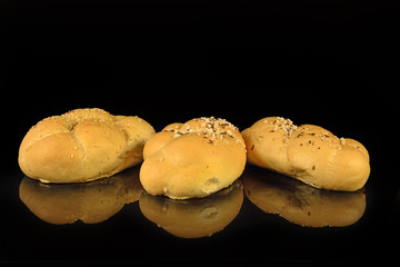 Freshly baked bun with seeds, salt and cumin on black background