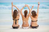 Fototapety Girls in bikinis sunbathing, sitting on the beach