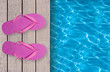 Swimming pool, wooden deck and pink beach shoes