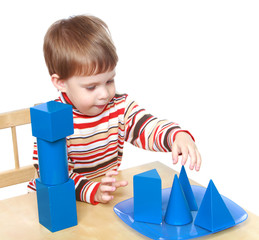 Little boy plays cubes and cones sitting at the table, Montessor