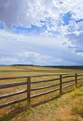 Wooden fence on a rural farm pasture fields