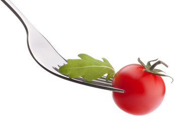 Fresh rucola  salad and cherry tomato on fork isolated on white