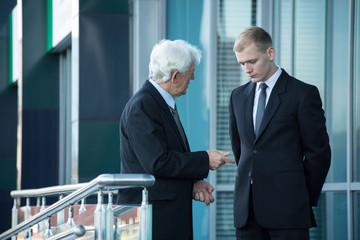 Senior businessman talking with his employee