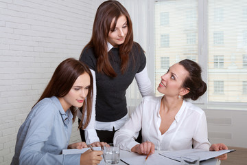 Three girls in formal clothes signing business documents