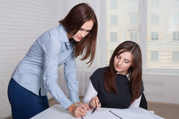 Couple of girls in formal clothes signing business documents