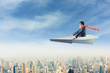 Man on paper airplane above the city