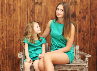 Lovely mother and little daughter in dress at home