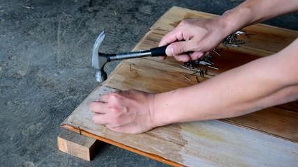 Carpenter nailing wood board