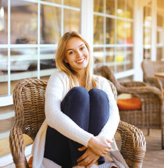 Pretty smiling woman sitting on armchair outdoors in city