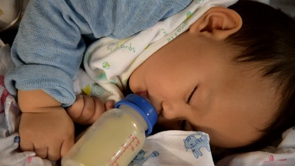 Baby boy drinking milk when sleeping