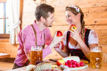 Paar bei Brotzeit auf Berghütte in Alpen