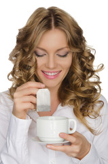 woman with tea bag looks into cup