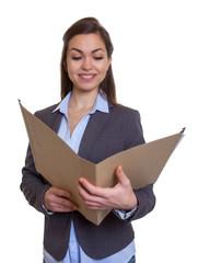 Geschäftsfrau im grauen Blazer studiert Akte