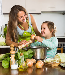 Woman with baby cooking at kitchen
