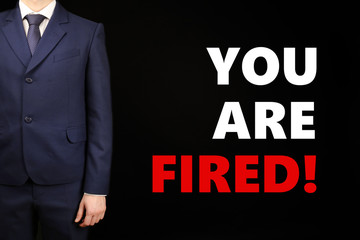 Businessman and text You Are Fired on black background