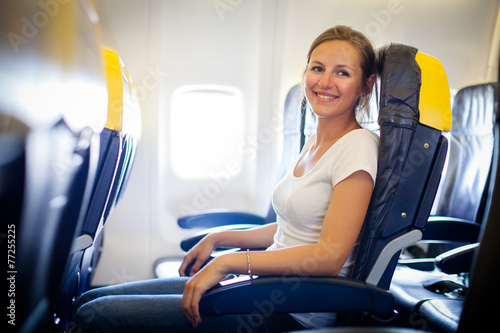 Pretty, young female passenger on board of an aircraft