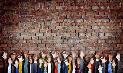 Group Diverse Hands Raised Brick Wall Concept