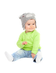 Beautiful baby  with wool hat sitting on the floor