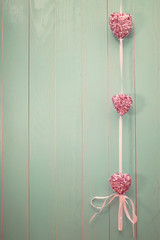 Pink shiny hearts on vintage green wood background