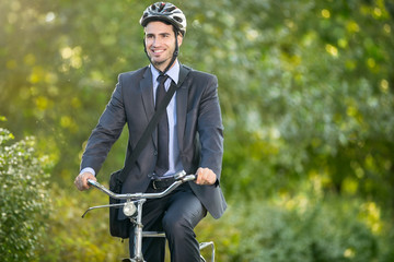 Positive young man riding a bicycle to work
