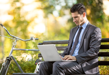 Businessman with bicycle working on laptop