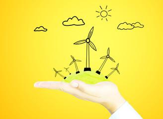 wind generator on green world by hand