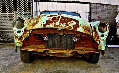 Old rusty retro car in the garage territory.