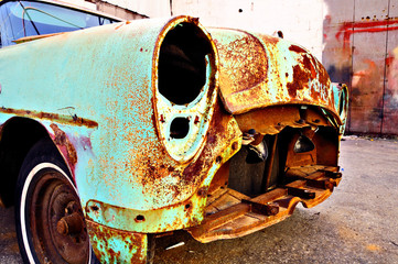 Old rusty retro car in the garage territory.