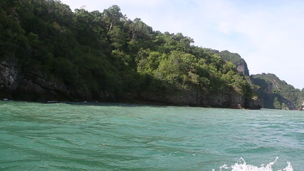 longtail thai motor boat sailing past the cliff island shore wit