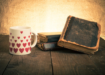 old books and a cup with hearts on a wooden table