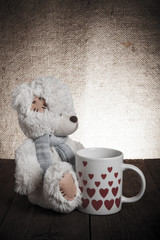 bear with a cup with hearts on the background of sacking