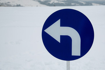 Turn left - road sign in the winter scenery