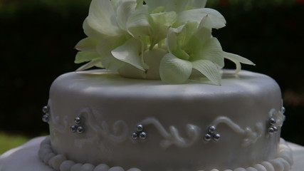 zoom on fresh white orchid and beads decorated wedding cake