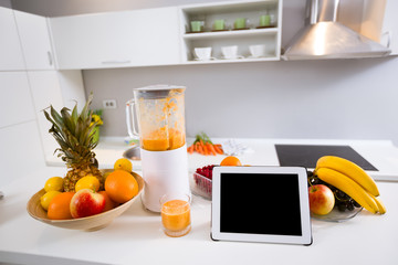 blender with fresh fruit drink and tablet pc