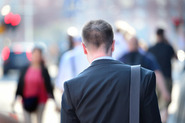 Suit in silhouette, sidewalk crowd