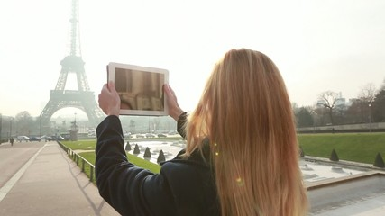 Young tourist photographing Eiffel tower with digital tablet