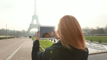 Woman in Paris takes picture with digital tablet