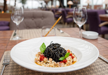 Black squid ink pasta with seafood on table